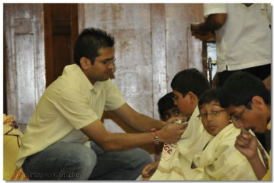Disciples help the children to prepare for pooja