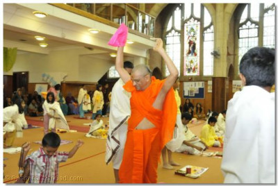 Acharya Swamishree show a young disciple how to do a 'Tap ni mara'