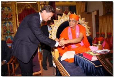 A sacred thread is tied on the wrist of Matthew Offord MP by Acharya Swamishree as an affirmation of bonding and friendship