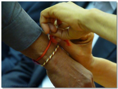 A sacred thread is tied on the wrists of guests by Acharya Swamishree as an affirmation of bonding and friendship