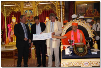 Acharya Swamishree presents a cheque of £12,000 to the patron of Phab Kidz, Ed 'Stewpot' Stewart
