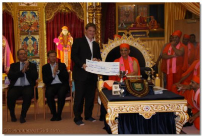 Acharya Swamishree presents a cheque of £13,000 to the patron of Sports Relief, Allan Pommery