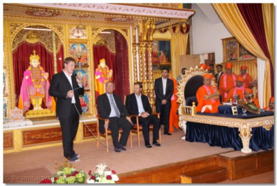 Allan Pommery addresses the congregation and commends Acharya Swamishree for inspiring charitable projects of the Temple