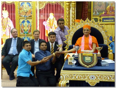 Swamibapa Volleyball Club receives the winners trophy from Acharya Swamishree