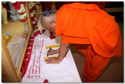 Acharya Swamishree blesses the new flag that is to be raised above the temple