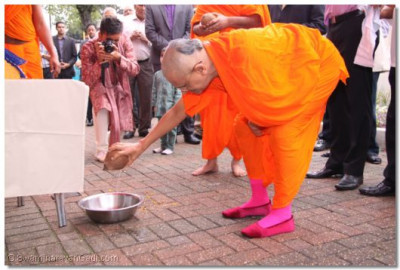 Acharya Swamishree continues the flag raising ceremony by breaking an auspicious coconut