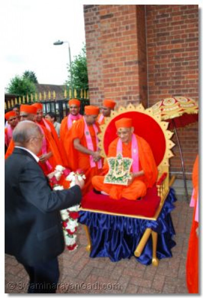 Acharya Swamishree is garlanded by the trustees of London Temple