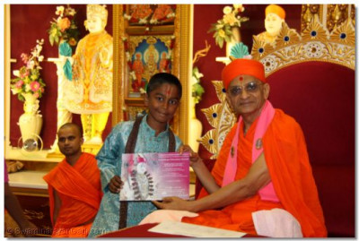 His Divine Holiness Acharya Swamishree presents a number of education achievement awards to young disciples