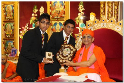 His Divine Holiness Acharya Swamishree presents the 1987 cricket league trophies to young disciples