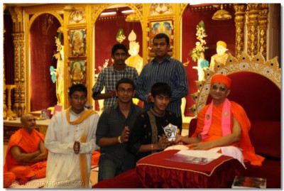 His Divine Holiness Acharya Swamishree presents the football league trophy to young disciples