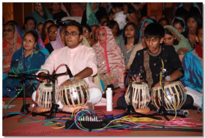 Talented young disciples skillfully perform playing traditional indian instruments to please Lord Shree Swaminarayanbapa Swamibapa and His Divine Holiness Acharya Swamishree