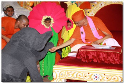 His Divine Holiness Acharya Swamishree blesses one of the young disciples dressed as an elephant