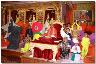 His Divine Holiness Acharya Swamishree gives darshan with the young disciples who performed in the dance