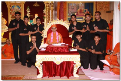 His Divine Holiness Acharya Swamishree gives darshan with members of Shree Muktajeevan Dhol Academy