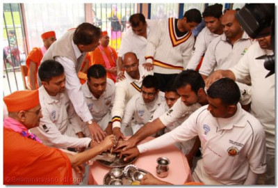 Disciples perform the welcoming ceremony by washing the divine feet of Lord Shree Swaminaryanbapa Swamibapa with the five nectars