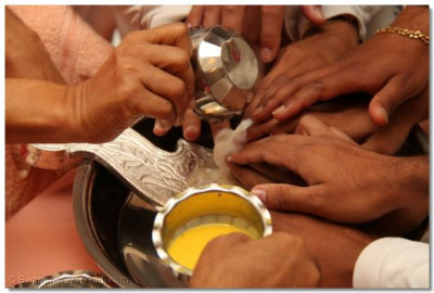 Disciples perform the welcoming ceremony by washing the divine feet of Lord Swaminaryanbapa Swamibapa with the five nectars