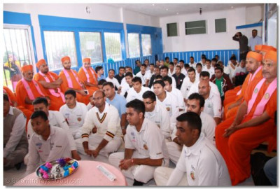 His Divine Holiness Acharya Swamishree showers his divine ashirwad as Sants and disciples listen attentively inside the Pavillion