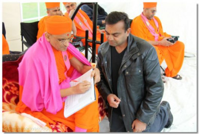 His Divine Holiness Acharya Swamishree inscribes the divine name of Lord Shree Swaminarayanbapa Swamibapa on the official unity cup scorebook