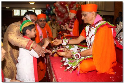 Acharya Swamishree gives chocolate to young disciples