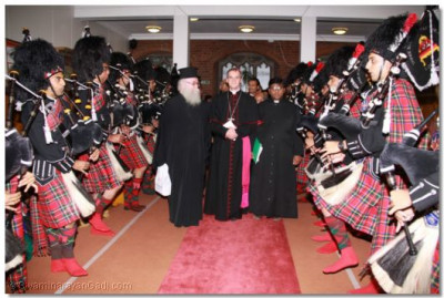Shree Muktajeevan Pipe Band forms a guard of honour as guests are welcomed into the temple