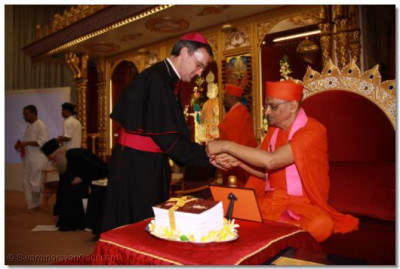 Acharya Swamishree ties the sacred thread of friendship on the wrist of Bishop Arnold Emissary of The Archbishop of the Diocese of Westminster