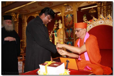 Acharya Swamishree ties the sacred thread of friendship on the wrist of Revd Khan Emissary of The Archbishop of Canterbury