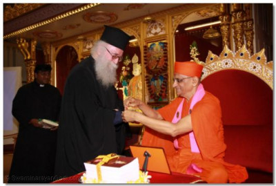 Acharya Swamishree ties the sacred thread of friendship on the wrist of Revd Deacon Meliton Oakes Emissary of The Archbishop of the Thyateira and Great Britain