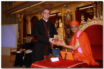 Emissary of The Archbishop of the Diocese of Westminster Bishop Arnold, presents the Holy Bible to Acharya Swamishree
