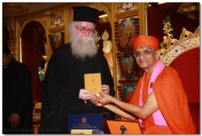 The Emmisary of the Archbishop Gregorios of Thyateira and Great Britain Revd Deacon Meliton presents the Holy Bible in Greek to Acharya Swamishree