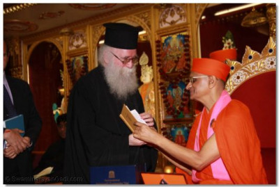 Acharya Swamishree reads the inscription in the Bilbe presented by the Emmisary of the Archbishop Gregorios of Thyateira and Great Britain Revd.Deacon Meliton