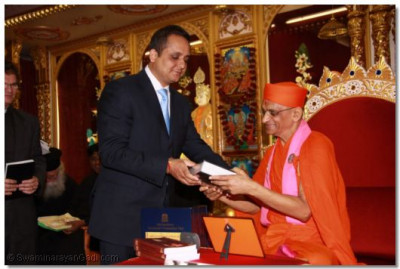 Mr Alnoor Samji, Council Member for External Affairs and Outreach, Aga Khan Insitute presents the Quran to Acharya Swamishree