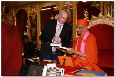 Mr Steven Derby (Faiths in Action) presents Acharya Swamishree with the Torah
