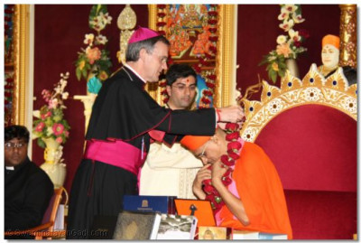 Emissary of The Archbishop of the Diocese of Westminster Bishop Arnold, presents a garland of flowers to Acharya Swamishree
