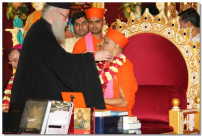 The Emmisary of the Archbishop Gregorios of Thyateira and Great Britain Revd Deacon Meliton presents a garland of flowers to Acharya Swamishree