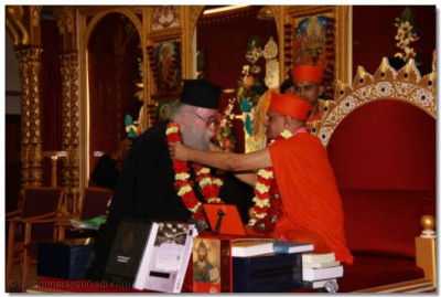 Acharya Swamishree presents a garland of flowers to the Emissary of The Archbishop of Thyateira and Great Britain Revd Deacon Meliton