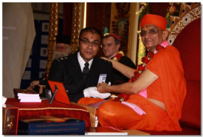 Acharya Swamishree presents the Metropolitan Warrant Card to Special Constable Vinod Khokhrai