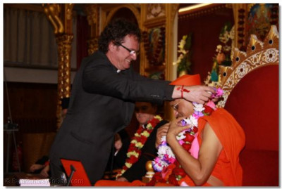 Revd Rex Morton (Vicar of Golders Green Parish Church) presents a garland of flowers to Acharya Swamishree
