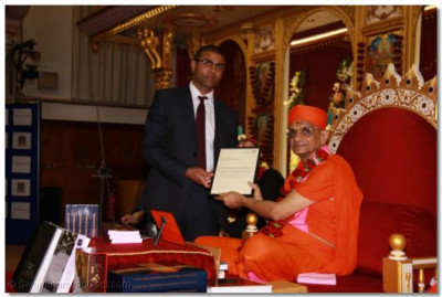 Acharya Swamishree is presented with a special letter of thanks from Dominic Sutherland from the NHS Blood Service