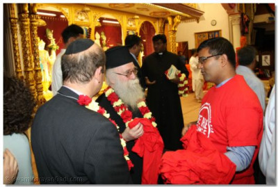 The Emmisary of the Archbishop Gregorios of Thyateira and Great Britain Revd.Deacon Meliton is presented with Sewa Day t-shirts by Vikas Pota of Sewa Day