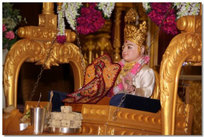 Divine darshan of Lord Swaminarayan seated on a gold swing