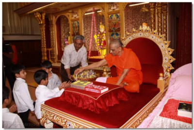 His Divine Holiness Acharya Swamishree consecrates the fruit and offers prasad to disciples