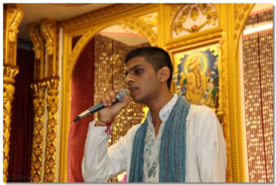A disciple sings a prathna to His Divine Holiness Acharya Swamishree, at the Bhakti Sangeet Night