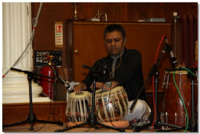 A devotee playing the tabla at the Bhakti Sangeet Night to accompany the kirtan.