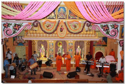 Sants and disciples sing devotional songs and play traditional and modern musical instruments during the raas