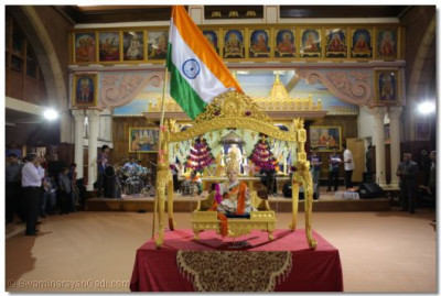 The Lord gave darshan draped and flanked by the Tiranga.
