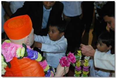 A youngs disciple gets an opportunity to place a garland on Jeevanpran Swamibapa