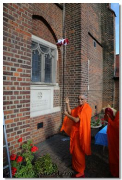 Acharya Swamishree performs the flag raising ceremony