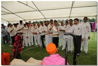 The cricket team perform aarti to Acharya Swamishree