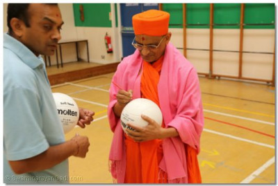 Acharya Swamishree signs a volleyball