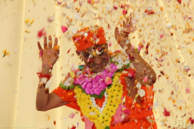 Acharya Swamishree is showered with flower petals to mark the conclusion of this historical event